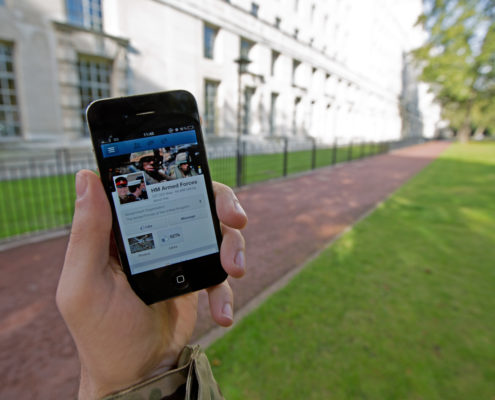 A serviceman accesses social media channels using a smart phone, outside MOD Main Building in London.